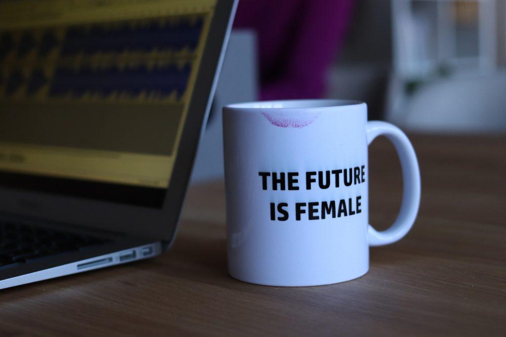 white and black printed ceramic mug beside laptop computer